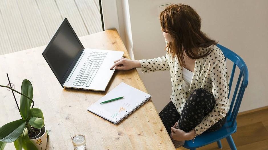Eine junge Frau arbeitet an ihrem Laptop.
