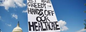 """Protest vor dem Kongress: """"Nimm deine gierigen Hände von unserer Gesundheitsversorgung"""", heißt es auf dem Plakat."""