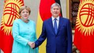 Bundeskanzlerin Angela Merkel wird in Kirgistans Hauptstadt Bischkek vom kirgisischen Präsidenten, Almasbek Atambajaw, begrüßt.