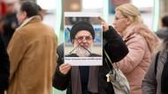 Eine Frau hält am Donnerstag im Terminal 1 auf dem Flughafen in Hamburg ein Foto mit dem Gesicht von Ayatollah Mahmoud Haschemi Schahroudi hoch.