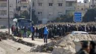 Warten in Homs: Beobachter der Vereinten Nationen steigen unter den Augen von Rebellen in Busse, die sie aus der Kampfzone bringen sollen.