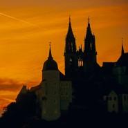 Die untergehende Sonne färbt den Himmel hinter dem Dom zu Meißen orangerot ein.