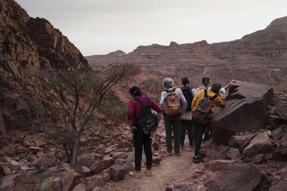 Touristinnen stehen auf einem Felsvorsprung und schauen in ein Bergtal in der Nähe von Wadi Sahw.