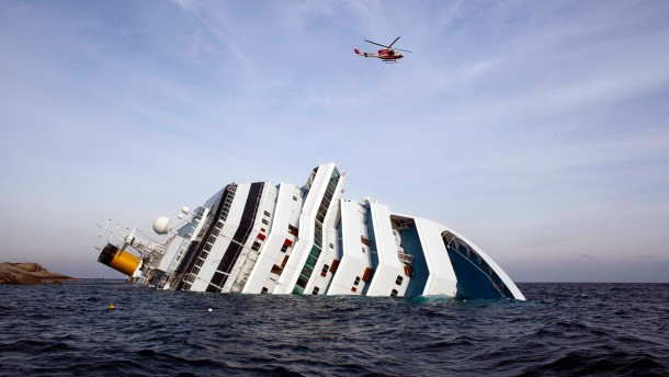 Firefighter helicopter flies over the Costa Concordia cruise ship after it ran aground off the west coast of Italy at Giglio island
