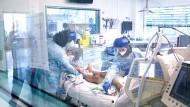 Auf der Intensivstation des Asklepios Klinikums Langen sind Pflegerinnen in Schutzkleidung bei der Versorgung eines Patienten zu sehen.