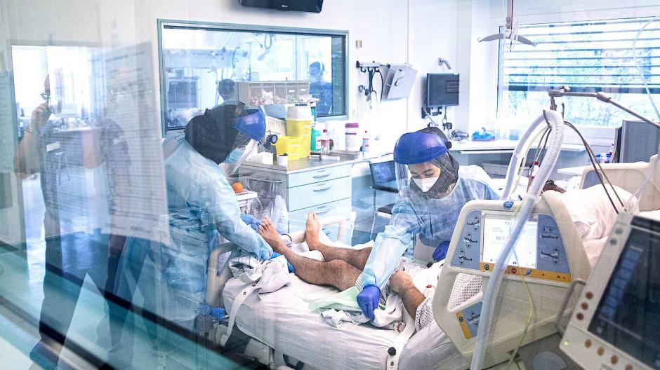 Pflegerinnen in Schutzkleidung bei der Versorgung eines Patienten auf der Intensivstation.