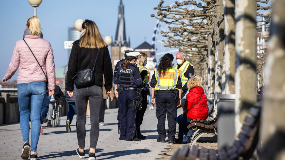 Spaziergänger am Düsseldorfer Rheinufer: Hier gilt seit neuestem ein Verweilverbot.
