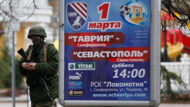 Armed man patrols near an advertisement for a local football match near the regional parliament building in the Crimean city of Simferopol