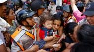 Das Leid der Massen: Eine Mutter mit Kind und Nudeln - mitten im Chaos vor einem Supermarkt in Caracas