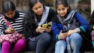 Das Handy ersetzt in Indien oft einen Scheidungsvertrag: Schülerinnen mit Smartphones vor einer Schule in Kalkutta