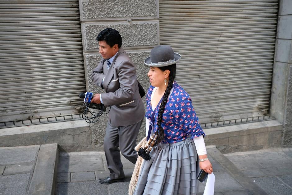 """Die aymara-stämmige Radiosprecherin und Youtuberin Yolanda Mamami, auch als """"Big Mouth Cholita"""" bekannt, läuft mit einem anderen Journalisten über den Marktplatz, um im Parlament von La Paz einige Abgeordnete zu interviewen. """"Indigene Probleme und Ideen sind nicht wirklich  in der Politik angekommen"""", sagte sie, """"Evo Morales hat sie zu einer folkloristischen Modenschau gemacht""""."""