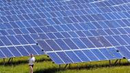 Ein Jogger vor einer Solaranlage im Ostallgäu