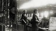 Zwei Frauen bei der Herstellung von Granaten in einer deutschen Munitionsfabrik. Foto um 1915.