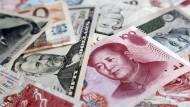Verschiedene Währungen: Im Fokus liegt ein Dollar- und Renminbischein