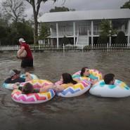 In Mandeville, Louisiana, treiben Personen in Schwimmreifen auf einer überfluteten Straße.