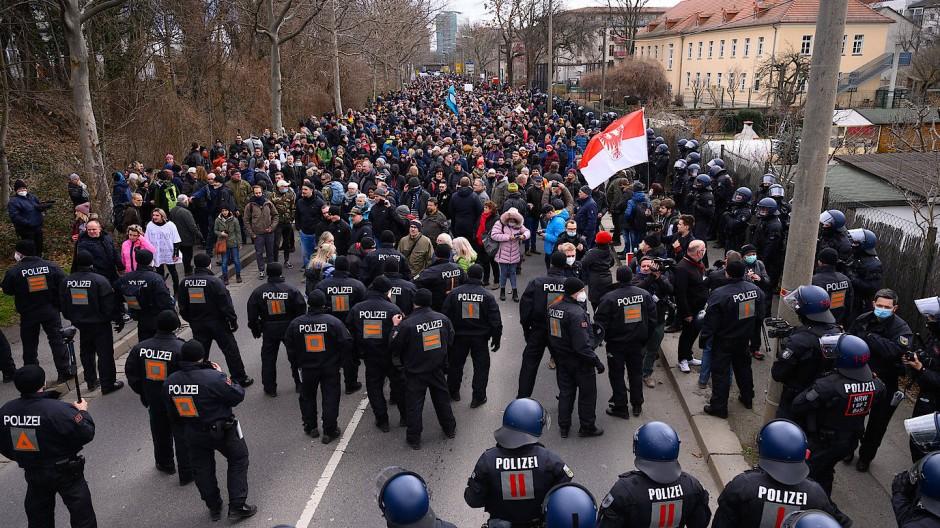 Polizisten und Demonstranten stehen in Dresden auf der Magdeburger Straße.