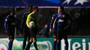 Referee Felix Brych of Germany holds the ball past Manchester United's players as their Champions League Group H soccer match against Braga was stopped due to a failure in the electricity power in Braga