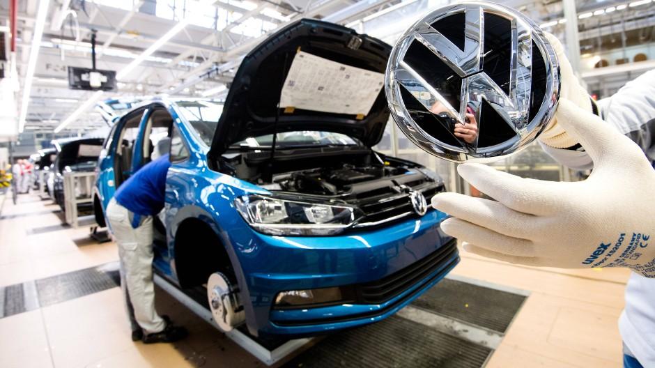 Ein Mitarbeiter zeigt ein VW Logo kurz vor Einbau in einen Volkswagen Touran in der Endmontage im VW Werk.