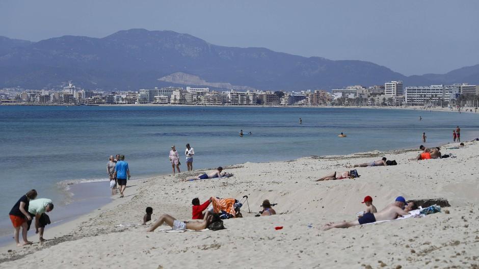 Menschen sonnen sich am Strand von El Arenal.