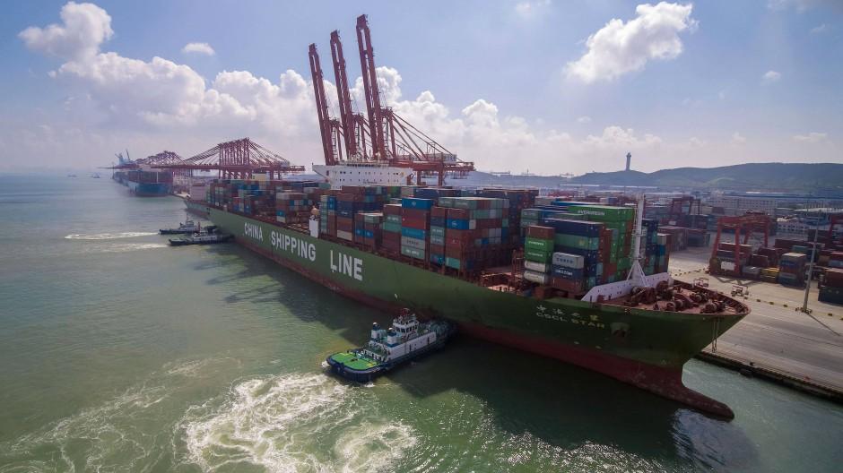 Schlepper bringen ein Containerschiff in der ostchinesischen Provinz Shandong an den Kai.