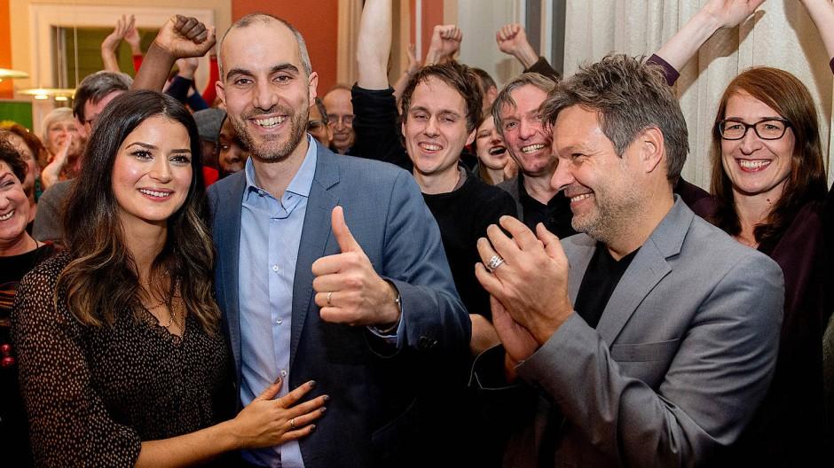 Belit Onay und seine Frau Derya freuen sich am Sonntagabend gemeinsam mit Grünen-Chef Robert Habeck (r.) über den Wahlsieg.