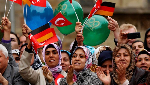 Turkish women wave German and Turkish flags during a visit of Turkey's President Gul in Osnabrueck