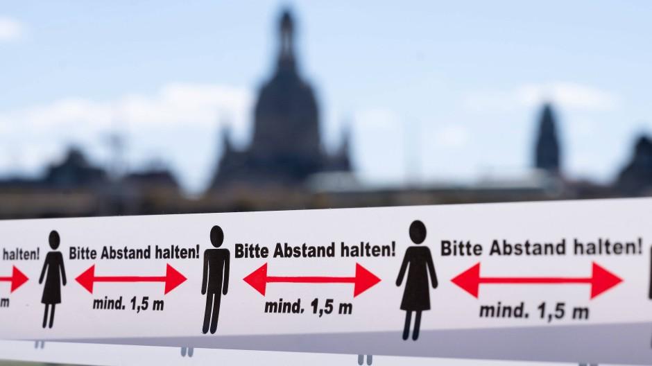 Ein Absperrband, das an den Corona-bedingten Mindestabstand erinnert, in Dresden