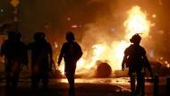 Rumänische Einsatzkräfte gehen während der Proteste in Bukarest an einer brennenden Straßensperre vorbei.