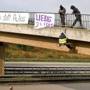 Umweltaktivisten hängen an einer Autobahnbrücke.