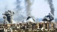 Rauch steigt nach dem Einschlag einer Rakete der syrischen Armee über Duma auf.