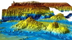 Diese dreidimensionale Karte des Meeresbodens im Suchgebiet von Flug MH370 zeigt im Hintergrund in braun den Broken Ridge, einen Bergrücken der bis auf 700 Meter an den Meerespiegel reicht. Von dort geht es in mehreren Stufen zum Teil sehr steil in den Diamantina Graben, der sich in dunkelblau quer durchs Bild zieht. Er ist mehr als 6000 Meter tief.