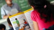 Ein Mädchen liest im islamischen Religionsunterricht in einem Schulbuch.