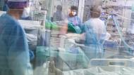 Ärzte und Pfleger in einem mit Corona-Patienten belegten Zimmer der Intensivstation des Asklepios Klinikums Langen.