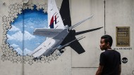 Was geschah an Bord von MH370? Ein junger Mann steht vor einer Wandmalerei in Kuala Lumpur, die das verschollene Flugzeug zeigt.