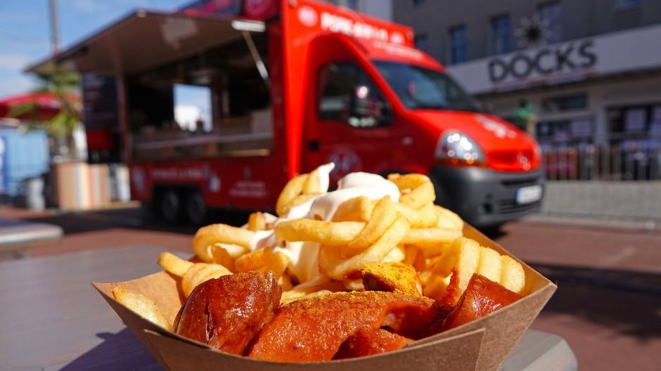 Currywurst und Pommes vor einem Foodtruck in Hamburg.