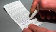 Ein Mann unterschreibt in Hamburg auf einem EC-Beleg die Ermächtigung zum Lastschrifteinzug.