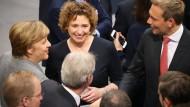 Begrüßung der Rückkehrer in den Bundestag: Bundeskanzlerin Angela Merkel gibt FDP-Generalsekretärin Nicola Beer und dem FDP-Vorsitzenden Christian Lindner (r.) die Hand.