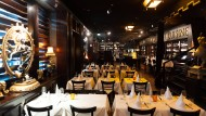 """Dunkle Täfelung und weiße Tischdecken: Blick in das Restaurant """"Ivory Club""""."""