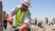 Flüchtlinge arbeiten im Irak an einer Natursteineinfriedung für eine neue Gemeinschaftsfläche.