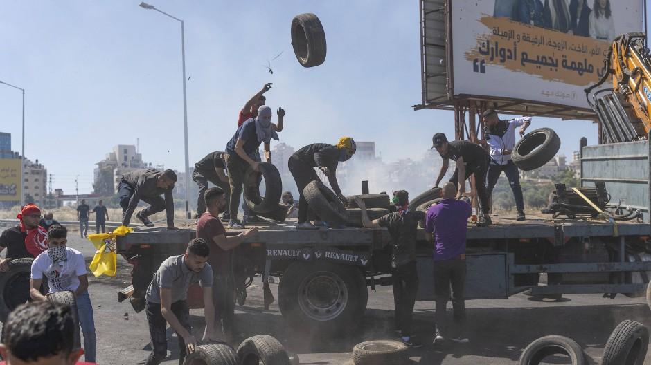 Protestierende Palästinenser im Westjordanland laden Reifen ab, um sie anzuzünden und eine Straße zu blockieren.