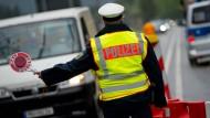 Bald Dienst an der Obergrenze? Ein Polizist kontrolliert in Bayern  aus Österreich einreisende Fahrzeuge.