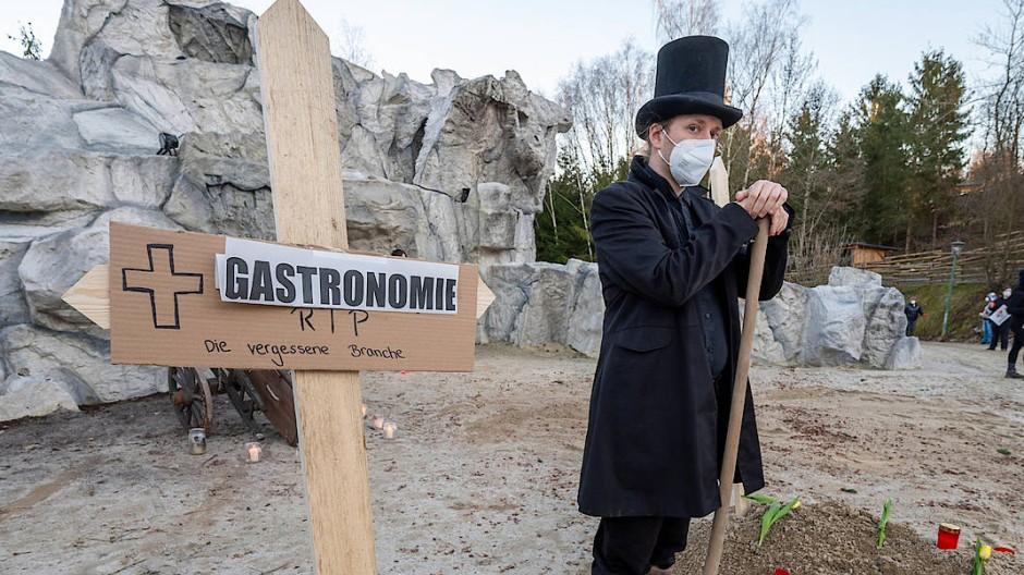"""Ein als Totengräber verkleideter Mann steht in Bayern neben einem Holzkreuz mit der Aufschrift """"Gastronomie""""."""
