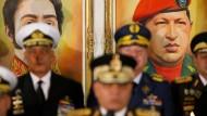 Die Porträts von Simón Bolívar und Hugo Chávez hängen an der Wand, während Venezuelas Verteidigungsminister Vladimir Padrino Lopez in Caracas am Donnerstag eine Pressekonferenz abhält