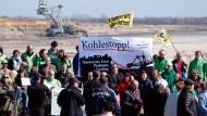 """Aktivisten der Bürgerinitiative """"Pro Pödelwitz"""" und von Umweltverbänden demonstrieren Ende März am Tagebau """"Vereinigtes Schleenhain""""."""