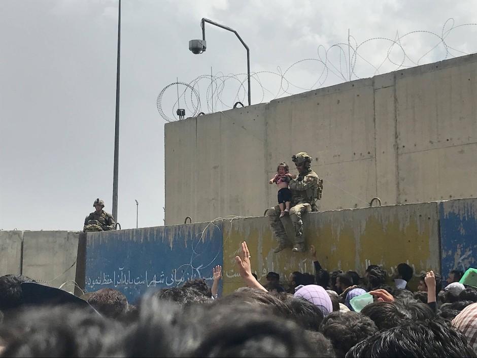 Während die Menschen vorwärts drängen, kommt ein Soldat näher und nimmt ein kleines Mädchen, um es vor dem Druck zu schützen. Zwei Stunden später schlossen die Streitkräfte das Tor.