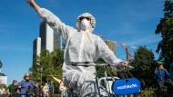Demonstranten der Fahrraddemo Sand im Getriebe treffen auf die Blockade vor dem Eingang der IAA und grüßen die anderen Protestler