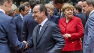EU-Gipfeltreffen in Brüssel: Frankreichs Präsident Hollande grüßt den estnischen Kollegen Roivas, im Hintergrund stehen Kanzlerin Merkel und Bettel aus Luxemburg.