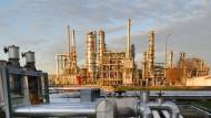 Sachsen-Anhalt, Leuna: Stahlrohre transportieren Rohöl aus Russland in die von der Abendsonne angestrahlten Produktionsanlagen einer Raffinerie.
