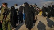 """Kämpfer der """"Demokratischen Kräfte Syriens"""" bewachen mehrere mutmaßliche Frauen von IS-Kämpfern."""