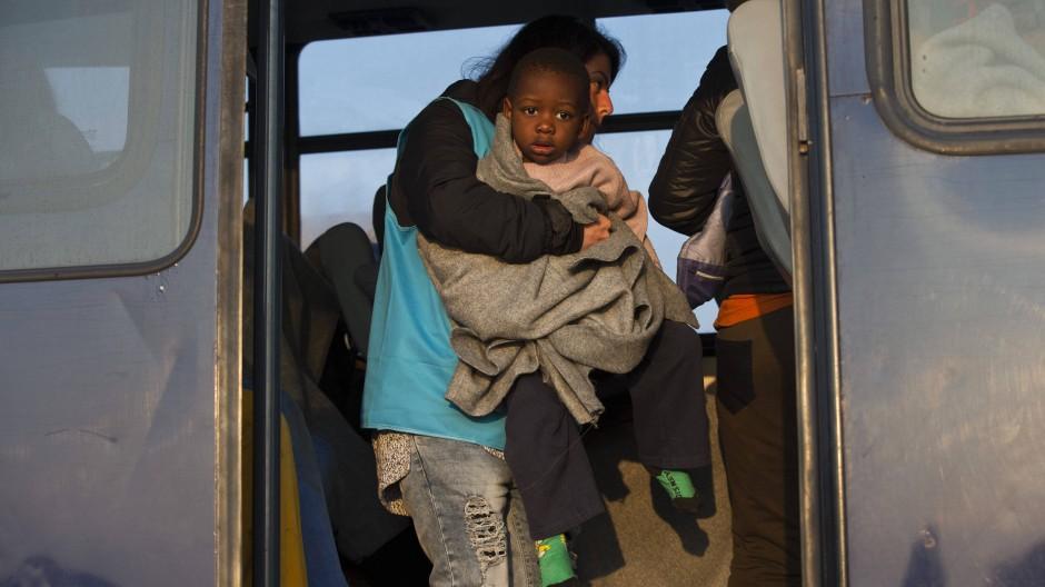 Eine Helferin trägt ein kleines Kind auf dem Arm, das in das Flüchtlingscamp Moria auf der griechischen Insel Lesbos gebracht werden soll